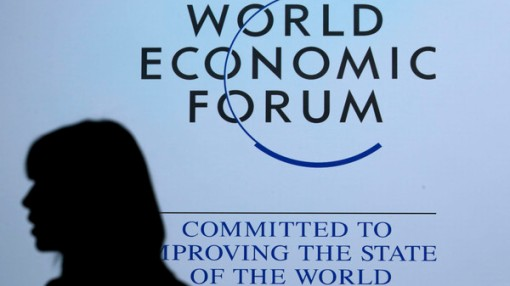 A delegate is silhouetted as she passes by a sign for WEF in Davos