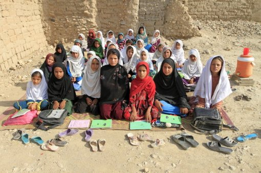 30 Sep 2015, Jalalabad, Afghanistan --- Teacher Mahajera Armani and her class of girls pose for a picture at their study open area, founded by Bangladesh Rural Advancement Committee (BRAC), outside Jalalabad city, Afghanistan September 19, 2015. Nearly three years after Taliban gunmen shot Pakistani schoolgirl Malala Yousafzai, the teenage activist last week urged world leaders gathered in New York to help millions more children go to school. World Teachers' Day falls on 5 October, a Unesco initiative highlighting the work of educators struggling to teach children amid intimidation in Pakistan, conflict in Syria or poverty in Vietnam. Even so, there have been some improvements: the number of children not attending primary school has plummeted to an estimated 57 million worldwide in 2015, the U.N. says, down from 100 million 15 years ago. Reuters photographers have documented learning around the world, --- Image by © PARWIZ/Reuters/Corbis