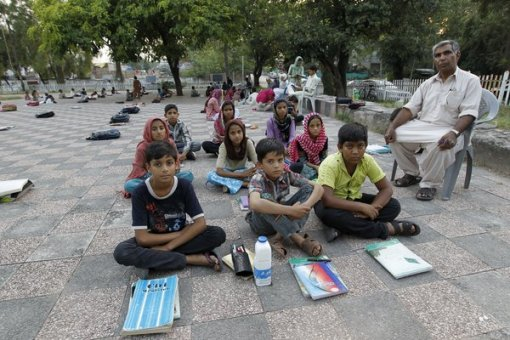 30 Sep 2015, Islamabad --- Master Mohammad Ayoub poses with his fifth grade students at a local park in Islamabad, Pakistan September 18, 2015. Ayoub, a Pakistani civil servant, started his programme to educate underprivileged children in 1985. Ayoub provides the educational supplies from his income as a civil servant while volunteers and his students teach the children English, Urdu and maths. Their classroom is in a local park during fair weather and a room in the local slum in the rainy season. Nearly three years after Taliban gunmen shot Pakistani schoolgirl Malala Yousafzai, the teenage activist last week urged world leaders gathered in New York to help millions more children go to school. World Teachers' Day falls on 5 October, a Unesco initiative highlighting the work of educators struggling to teach children amid intimidation in Pakistan, conflict in Syria or poverty in Vietnam. Ev --- Image by © CAREN FIROUZ/Reuters/Corbis