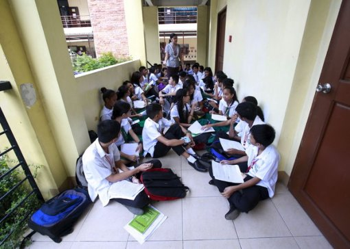 30 Sep 2015, Manila, Luzon Island, Philippines --- Teacher Kristine Passag holds a Values Education class for Grade 9 students in a hallway of Timoteo Paez High School in metro Manila, Philippines, September 15, 2015. Passag says she is temporarily holding classes in hallways while waiting for the completion of a new school building to address the shortage of classrooms. Nearly three years after Taliban gunmen shot Pakistani schoolgirl Malala Yousafzai, the teenage activist last week urged world leaders gathered in New York to help millions more children go to school. World Teachers' Day falls on 5 October, a Unesco initiative highlighting the work of educators struggling to teach children amid intimidation in Pakistan, conflict in Syria or poverty in Vietnam. Even so, there have been some improvements: the number of children not attending primary school has plummeted to an estimated 57 million worldwide in 2015, --- Image by © ROMEO RANOCO/Reuters/Corbis