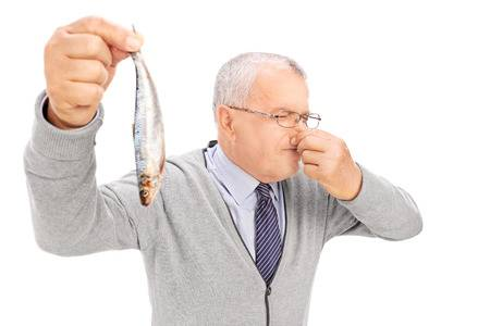 31619002-senior-gentleman-holding-a-rotten-fish-isolated-on-white-background.jpg